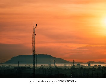 cctv camer security on tall pole standing for monitoring petrochemical plants in morning with moutain,fog and orange sky background.