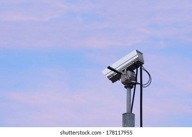 CCTV camera against a blue and pink evening sky.