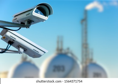 CCTV camera concept with refinery on blurry background