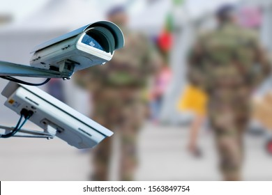CCTV camera concept with soldiers on patrol on blurry background