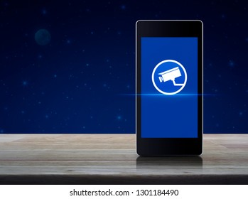 cctv camera flat icon on modern smart mobile phone screen on wooden table over fantasy night sky and moon, Business security and safety online concept
