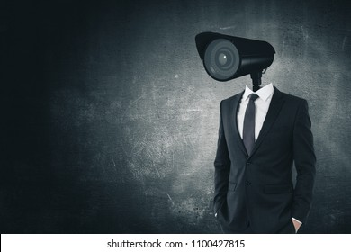CCTV camera headed businessman standing on dark concrete background with copy space. Supervision and spy concept