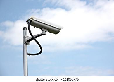 CCTV camera on blue sky background.