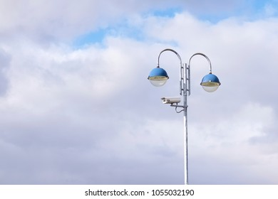CCTV camera on post against large blank blue sky clouds space and two lights on road street for security and reduce crime neighbourhood watch scheme