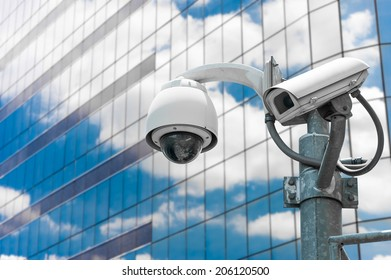 CCTV camera or surveillance operating with glass building in background