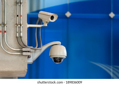 CCTV camera or surveillance operating on blue wall background