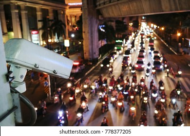 The CCTV camera, surveillance,  operating on traffic road on the juntion in night time in Bangkok, Thailand. Selective focus with blurred background. Low key. Transpotation and technology concept.
