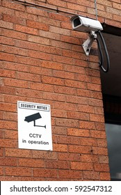 CCTV camera and warning notice on urban red brick wall. London Docklands