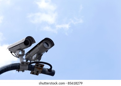 CCTV cameras on high towers in the background sky.