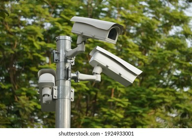 CC.TV. cameras on metal pole in public park for monitor, observe and record evident of incident for investigation and prevent criminal.  Safety, CC.TV. camera concept.                               - Shutterstock ID 1924933001