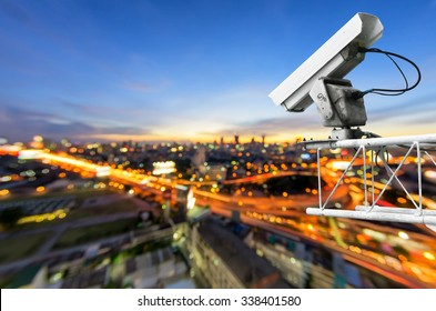 CCTV cameras, security cameras. With the backdrop tail lights blurred on the road from a high angle.