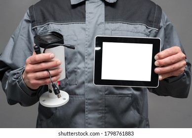 CCTV installation worker with a security camera and blank screen digital tablet close up.