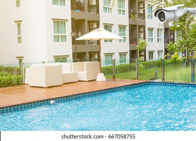 CCTV and relaxing rattan chairs with pillows beside swimming pool.