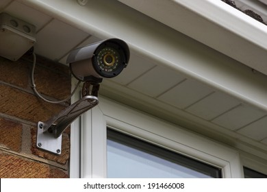 CCTV security camera for home protection, privacy, security against crime & surveillance, mounted on house exterior wall.