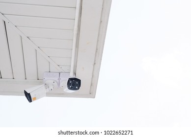 CCTV security camera on the ceiling and blue sky background.