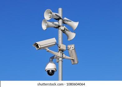 CCTV security cameras and loudspeakers against blue sky