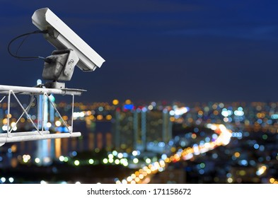 CCTV security on the building. Below is a view of the city lights at night, focus blur.
