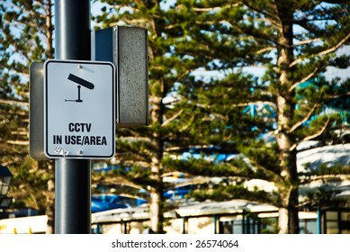 A CCTV sign on a post with trees in the background.