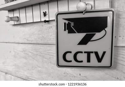 CCTV sign security camera at wood wall in house, grey photo for security concept.