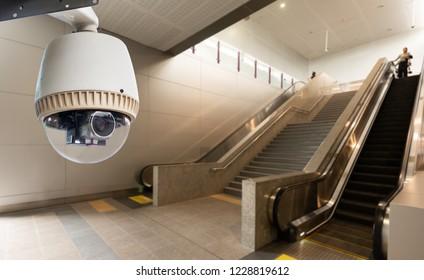 CCTV surveillance camera operating in front of escalator in building