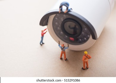 CCTV surveillance security camera with worker doing maintenance or installing.