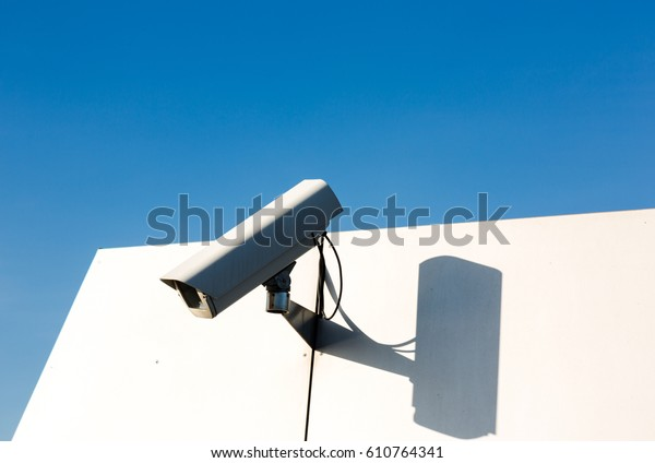 CCTV video camera on private property recording surroundings. Close up horizontal shot with white wall and blue sky in background