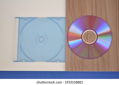 CD cover with CD beside on white and wooden base in top view in color photo