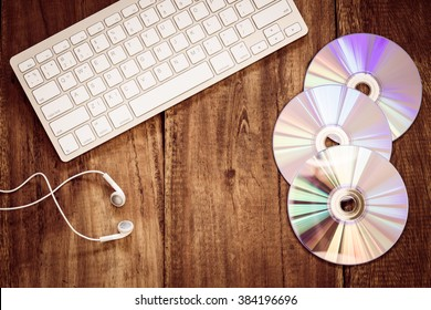 CD, earphones & computer keyboard on wooden table + vintage filter for music technology concept