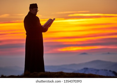 Ceahlau, ROMANIA - 09 February 2019:Silhouettes of a priest reading from the book in the light of sunset, Romania