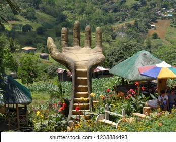 CEBU CITY, PHILIPPINES—MARCH 2018: Giant concrete man's hand surrounded by native cottages and colorful flowers at Sirao Gardens, a popular destination in Cebu City.