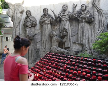 CEBU CITY, PHILIPPINES—MARCH 2018: A woman lights a a candle at the Sto. Niño in Cebu City. In view are the sculptures on the wall.
