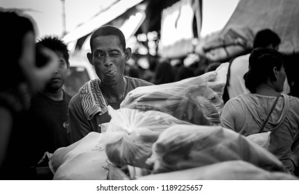 Cebu City, Philippines October 8 2017: man delivers a bag of vegetables while doing wacky face.
