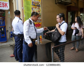 CEBU CITY, PHILIPPINES--MARCH 2018: A security guard checks the backpack of a man at the entrance to the Basilica del Sto Niño Church in Cebu City.