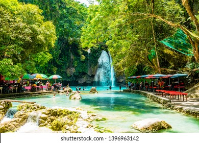 Cebu / Philippines - April 02 2019: People swimming in water at Kawasan Falls, turquoise waterfalls, area with cafes
