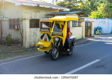 Cebu / Philippines - April 04 2019: everyday life of locals. People riding in local public transport - tricycle