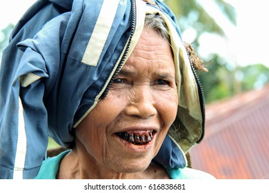CECER VILLAGE, INDONESIA-APR. 21,2014:  A senior woman shows tourists visiting Flores Island her teeth. Staining and rotting have occurred as a result of a lifetime of chewing the addictive betel nut.