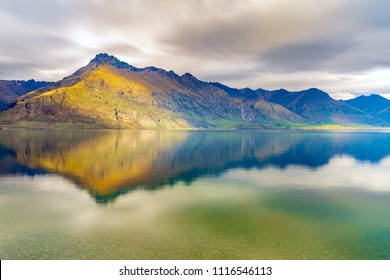 Cecil peak and Walter peak mountain range on the lakeside of lake Wakatipu in cloudy day. Seen from Wilson bay, Queenstown, Otago region, South Island, New Zealand.