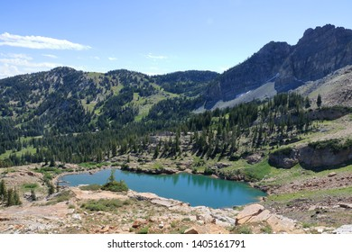 Cecret Lake located in a glacial bowl, shows its clear waters during late summer near Alta, Utah.