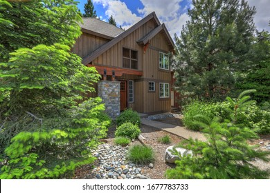 Cedar brown mountain home with great landscaping and rocks, modern lines of the front exterior during summer.