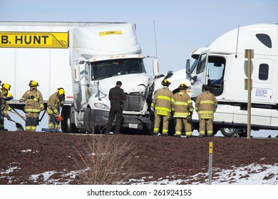 Cedar City, UT, USA - February 5, 2014: Firefighters and a police officer on the scene of an accident near the I15 exit.