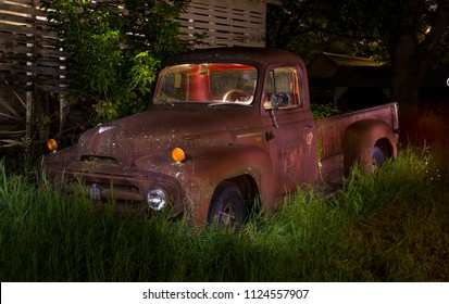 Cedar, MN/USA 06/27/18 Dark night shot of rusty old 1940s pickup truck out in field. Light painted out on farm, cab lit from within; grass and corn crib in background.
