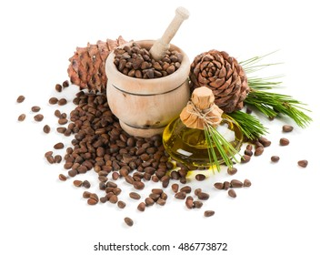 Cedar pine nuts in a mortar, cones, oil, cedar brunch isolated on white background.