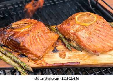 cedar plank salmon with lemon cooking on a grill