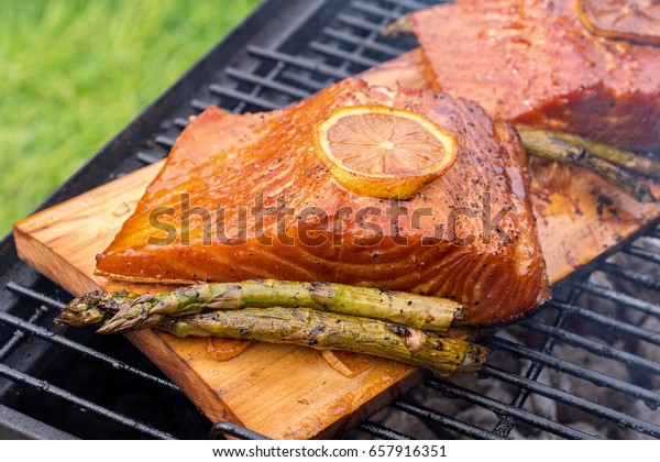 cedar plank salmon with lemon cooking on grill