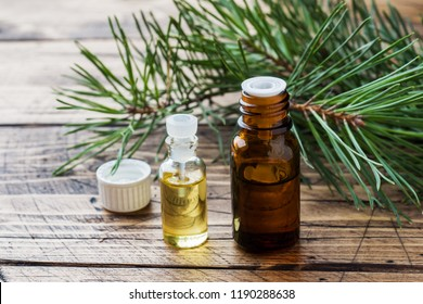 Cedar and spruce essential oil in small glass bottles on wooden background. Selective focus