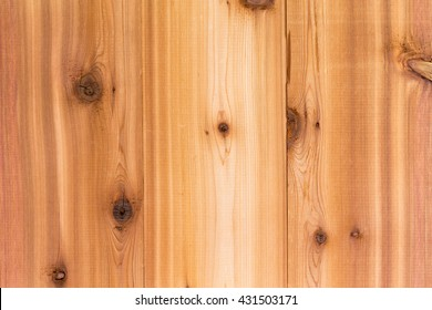 Cedar wood background texture with vertical boards and a decorative woodgrain pattern with natural knots, full frame view