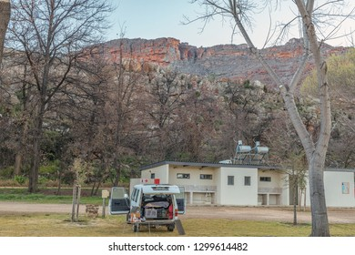 CEDERBERG, SOUTH AFRICA, AUGUST 24, 2018: The camping site at Sanddrif Holiday resort in the Cederberg Mountains. The Wolfberg Cracks, a vehicle and an ablution building are visible