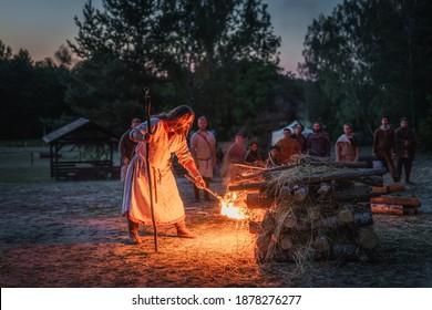 Cedynia, Poland, June 2019 Pagan reenactment of Kupala Night, called in Poland Noc Kupaly, shaman ignite bonfire. Slavic holiday celebrated on the shortest night of the year