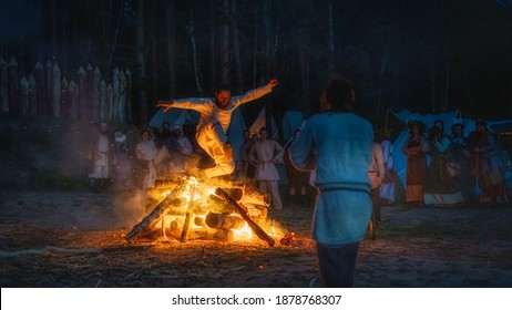 Cedynia, Poland, June 2019 Pagan reenactment of Kupala Night, called in Poland Noc Kupaly, man showing his bravery is jumping over bonfire. Slavic holiday celebrated on the shortest night of the year