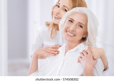 Ceerful aged woman embracing with her daughter